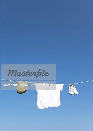 T-shirt, chapeau et chaussures suspendu à une corde à linge