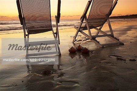 Chaises de plage avec des lampes à huile sur la plage