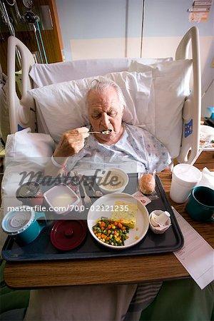 Man Eating Hospital Food in Hospital Bed