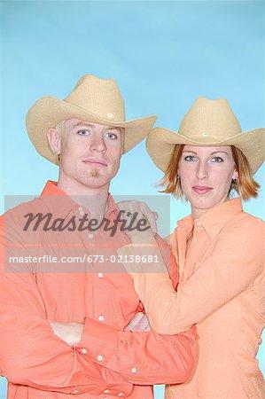 Jeune couple portant des chapeaux de cowboy
