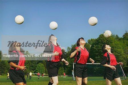 Vier junge weibliche Fußball-Spieler Position der Bälle