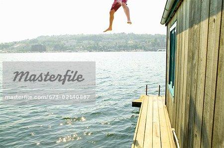 Jambes d'homme sautant dans l'eau