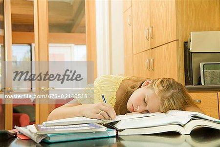 Adolescente, dormant sur les manuels scolaires
