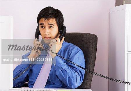 Homme d'affaires parlant sur deux téléphones en même temps