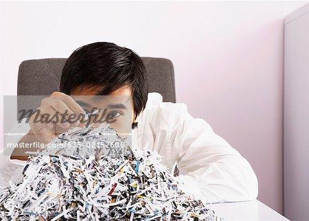 Homme d'affaires examinant le papier déchiqueté
