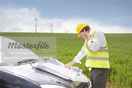 Homme sur mobile sur un parc éolien
