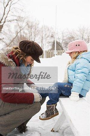 Mère aider fille Put sur patins à glace