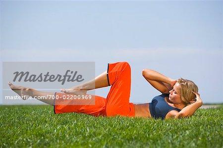 Frau tut Bauch Crunches im Park