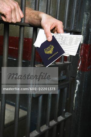 Man in Prison Holding Passport