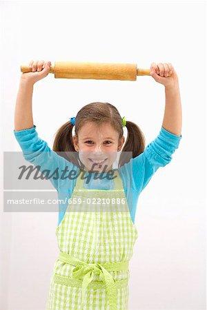 Fille en tablier avec de la farine sur son visage en tenant le rouleau à pâtisserie