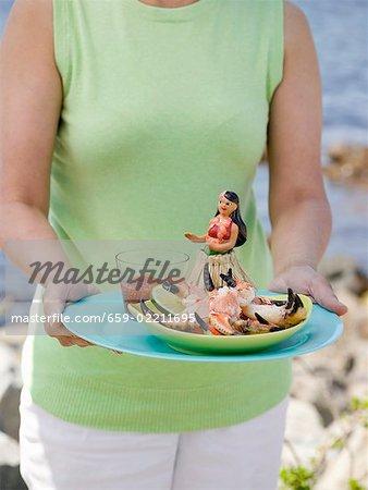 Femme tenant la plaque de crabe griffes et trempette sur la plage