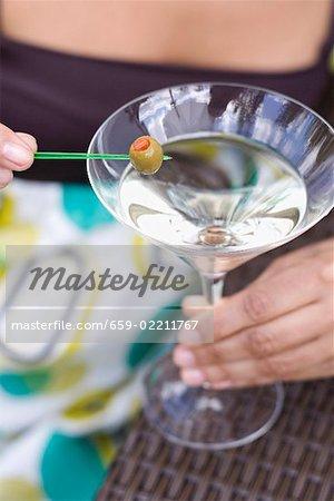 Femme tenant vert olive sur cocktail bâton sur le verre à Martini