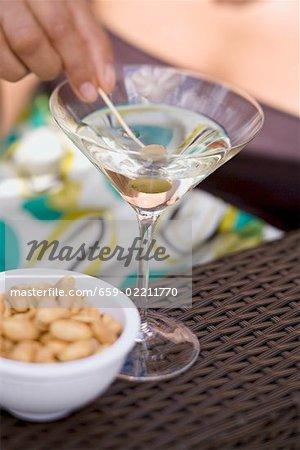 Femme tenant vert olive sur cocktail bâton en verre à Martini