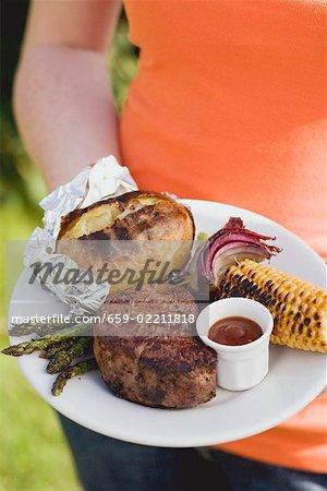 Femme tenant une assiette de steak grillé et accompagnements