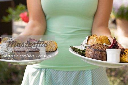 Femme au service de deux plaques de bifteck grillé & accompagnements