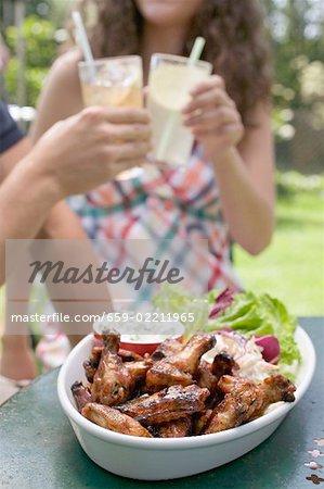 Brathähnchen Flügel mit Salat, junge Menschen im Hintergrund