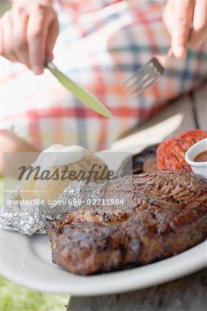 Femme, manger un steak grillé avec des pommes de terre au four