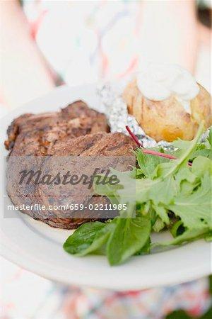 Femme tenant l'assiette de steak grillé, pomme de terre au four & salade