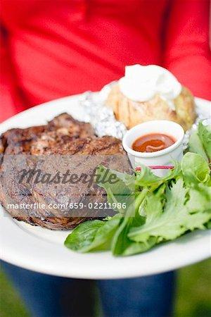 Personne qui détient l'assiette de steak grillé, pommes de terre au four & salade