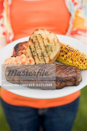 Femme tenant un plat de boeuf, pain, maïs en épi, fèves au lard