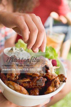 Main atteignant pour ailes de poulet grillé