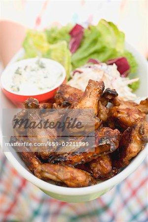 Frau hält Hähnchenflügel mit Blauschimmelkäse Dip und Salat