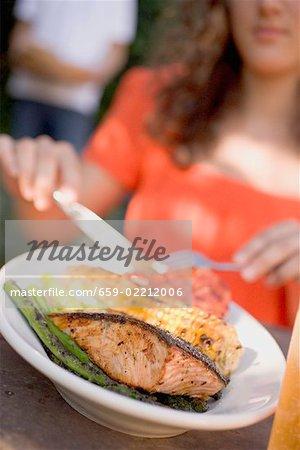 Femme mangeant saumon grillé avec maïs sur l'épi & légumes