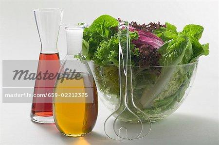 Huile & vinaigre en carafes à côté du bol à salade, salade