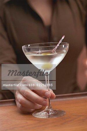 Femme tenant le verre de Martini avec olive