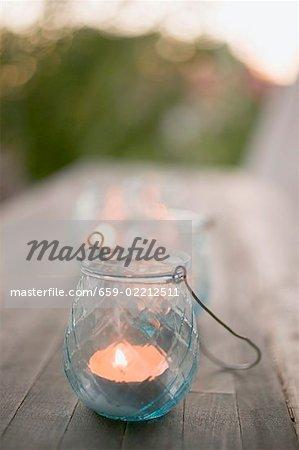 Windlight on wooden table in garden