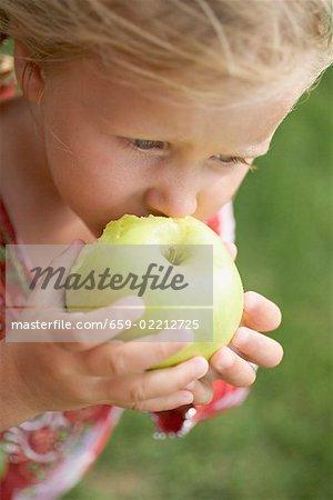 Petite fille mangeant une grosse pomme verte