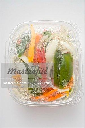 Tranches de légumes dans le récipient en plastique (vue aérienne)