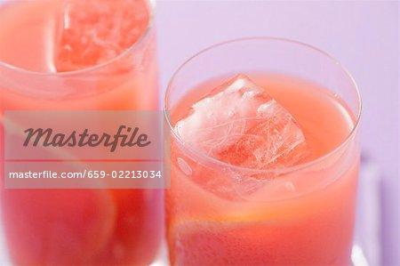 Deux verres de jus de pamplemousse rose avec des cubes de glace