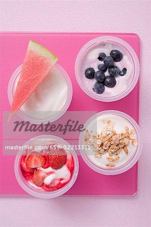 Assortiments d'yaourts avec baies, melon et céréales