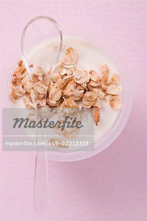 Yaourt avec des céréales dans un pot en plastique avec cuillère