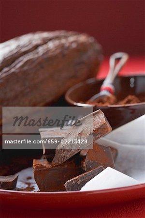 Stück Schokolade vor Kakao Pulver & Kakao-Frucht