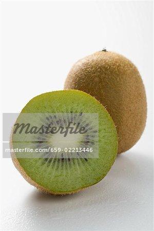 Ganze Kiwi-Früchte und eine halbe Kiwi-Frucht