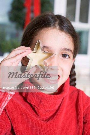 Mädchen mit ausgeschnittenen Keks vor ihrem Auge