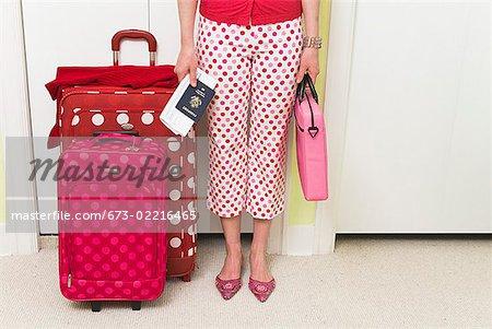 Femme debout avec pois assortis aux motifs valises
