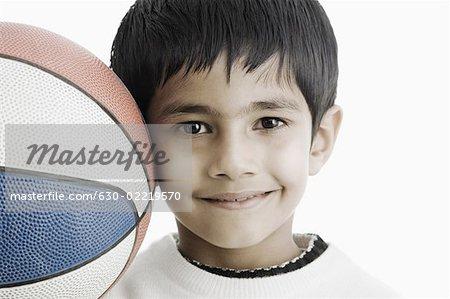 Portrait d'un garçon tenant un ballon de basket