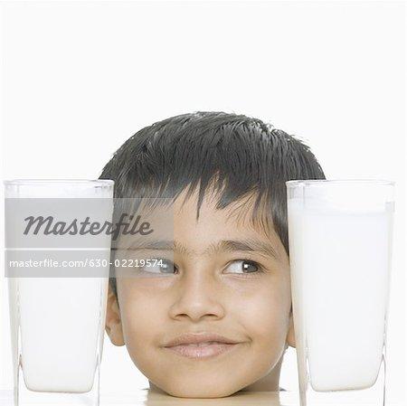 Gros plan d'un garçon regardant les verres de lait