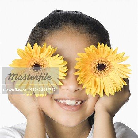 Gros plan d'une jeune fille se cachant son visage avec fleurs et souriant