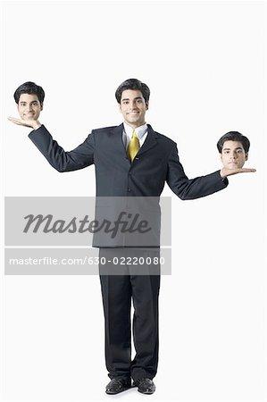 Portrait d'un homme d'affaires équilibrer deux têtes sur son palm