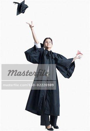 Jeune diplômé femelle jetant son Conseil de mortier dans l'air