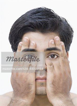 Portrait d'un jeune homme qui couvre ses yeux avec ses mains