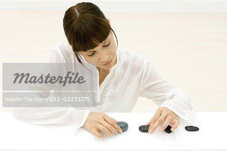 Femme organisant la rangée de pierres, regardant vers le bas