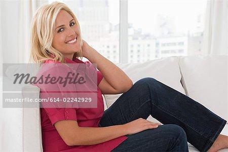 Portrait d'une femme assise sur un sofa
