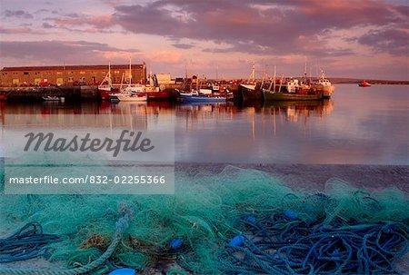 Jetée de Kilronan, Inishmore, îles d'Aran, County Galway, en Irlande ; Bateaux ancrés et filets de pêche