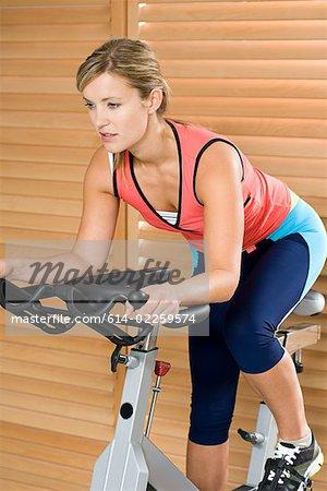 Femme sur le vélo d'exercice