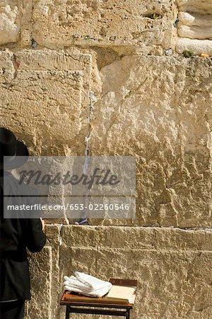 Un homme en prière au mur des lamentations